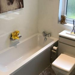 Stylish re-design in this bathroom with Grey matt doors and panels and white quartz wall panels